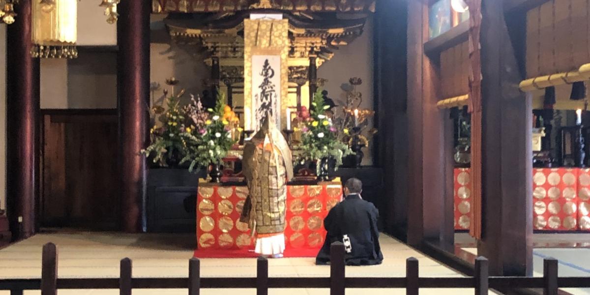 祖師執筆の名号(南無阿弥陀仏の掛け軸)を前に祈念される御導師